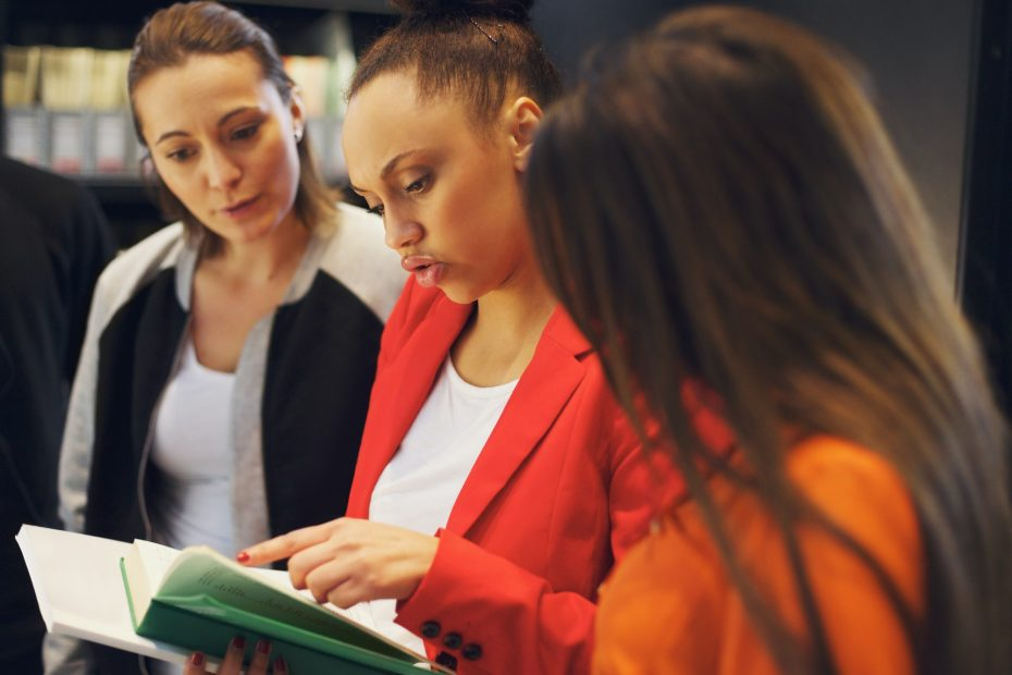 Young people in library looking at a book together